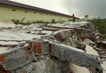 A guard walks on the ruins of prison wall which collapsed during yesterday's quake in Banda Aceh, April 12, 2012. REUTERS/Beawiharta