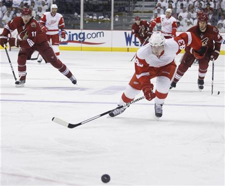 Detroit Red Wings Darren Helm skates ahead of Phoenix Coyotes Martin Hanzal (L) and Adrian Aucoin for the puck in the third period during Game 2 of their NHL Western Conference quarter-final hockey game in Glendale, Arizona April 16, 2010. REUTERS/Joshua Lott