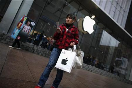 A customer walks out after shopping at an Apple store in downtown Shanghai February 28, 2012. REUTERS/Carlos Barria/Files