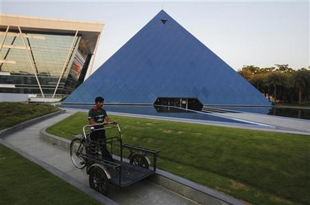 A man pushing a tricycle cart walks in front of a pyramid-shaped building made out of glass in the Infosys campus at Electronics City in Bangalore, February 28, 2012. REUTERS/Vivek Prakash/Files
