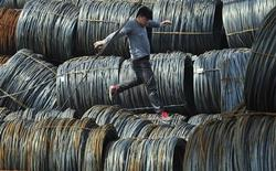 A labourer walks on coils of steel wire at a steel market in Shenyang, Liaoning province April 13, 2012. China's economy grew at its slowest in nearly three years in the first three months of 2012, with a weaker than expected reading raising investor concerns that a five-quarter long slide has not bottomed and that more policy action would be needed to halt it. REUTERS/Sheng Li