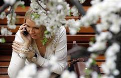 Женщина говорит по телефону в украшенном цветами ГУМе в Москве, 4 марта 2011 г. Наступающие выходные, праздничные для православных россиян, принесут в Москву весеннее потепление - на Пасху в столице ожидается до плюс 15 градусов. REUTERS/Denis Sinyakov