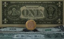 Монета в один евро на фоне долларовой банкноты в Мадриде, 17 ноября 2011 г. Евро снижается на фоне повышения доходности гособлигаций Испании, хотя вряд ли выйдет из установившегося в последние месяцы диапазона к доллару. REUTERS/Sergio Perez