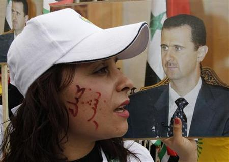 A supporter of Syrian President Bashar al-Assad carrying his image, with words written on her face that reads in Arabic ''Bashar I love you'', takes part in a rally to commemorate the 65th anniversary of the foundation of the Baath Party, at al-Sabaa Bahrat square in Damascus April 7, 2012. REUTERS/Khaled al-Hariri