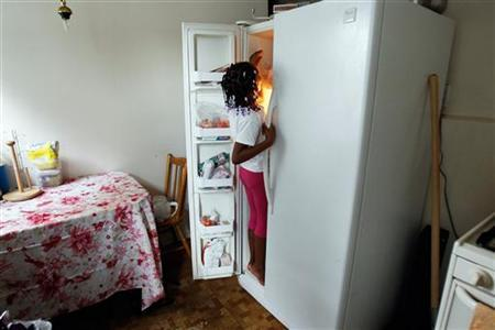 Tashawna Green's daughter Taishaun, 6, reaches into the freezer for an ice pop at her home in Queens Village, New York August 21, 2011. REUTERS/Jessica Rinaldi