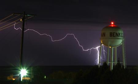 A lightning strike is seen near the water tower of Benkelman, Nebraska April 12, 2012. REUTERS/Gene Blevins