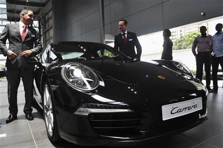 Company representatives stand beside a vehicle by German carmaker Porsche in Lagos March 14, 2012. REUTERS/Monica Mark