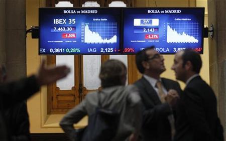 Traders look at computer screens at Madrid's bourse April 12, 2012. REUTERS/Andrea Comas