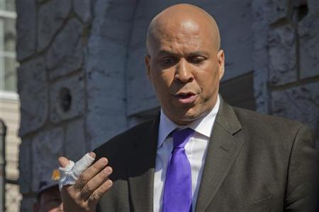 Newark Mayor Cory Booker speaks to the media outside a burned house in Newark, New Jersey, April 13, 2012. REUTERS/Eduardo Munoz