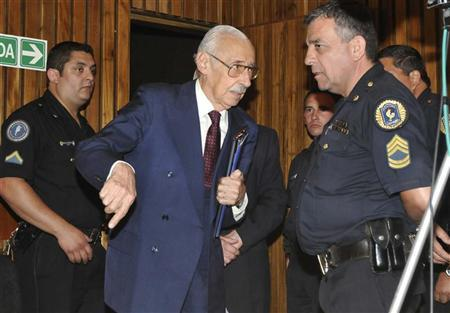 Former Argentine dictator Jorge Rafael Videla (C) is escorted out the courtroom after listening to the verdict in his trial at a courthouse in the province of Cordoba December 22, 2010. REUTERS/Tribunal Federal/Handout