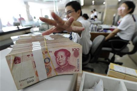 An employee reaches for a bundle of 100 yuan banknotes at a branch of Bank of China in Hefei, Anhui province September 17, 2010. REUTERS/Stringer