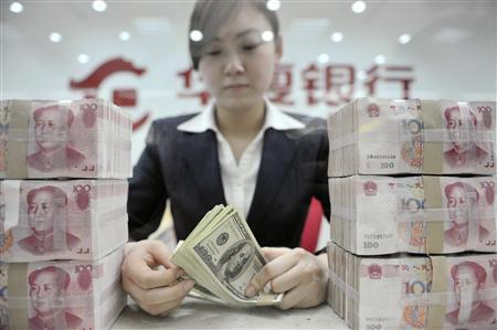 An employee counts U.S. dollar banknotes at a branch of Huaxia Bank in Shenyang, Liaoning province in this March 18, 2010 file photo. China took a milestone step in turning the yuan into a global currency on April 14, 2012, by doubling the size of its trading band against the dollar, pushing through a crucial reform that further liberalises its nascent financial markets. REUTERS/Sheng Li/Files