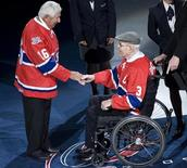 Former Montreal Canadiens Butch Bouchard (3) and Elmer Lach (16) shake hands during a NHL hockey pre-game ceremony in Montreal, October 15, 2008. REUTERS/Christinne Muschi