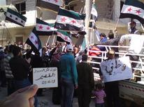 Demonstrators, with the Syrian opposition flags, protest against Syria's President Bashar Al-Assad after Friday prayers in Al Qasseer city, near Homs April 13, 2012. REUTERS/Shaam News Network/Handout