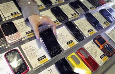 An employee takes a Nokia mobile phone at a shop in downtown Milan April 12, 2012. REUTERS/Alessandro Garofalo