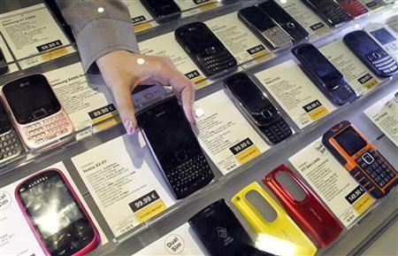 An employee takes a Nokia mobile phone at a shop in downtown Milan April 12, 2012. REUTERS/Alessandro Garofalo