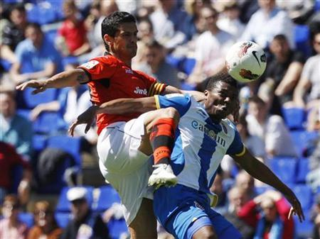 Espanyol's Kalu Uche (R) fights for the ball with Valencia's Ricardo Costa during their Spanish First division soccer league match at Cornella-El Prat stadium, near Barcelona April 15, 2012. REUTERS/Albert Gea