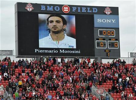 Toronto FC fans stand for a moment of silence in honor of Livorno's Piermario Morosini before the team's MLS soccer match against Chivas USA in Toronto April 14, 2012. Morosini died after collapsing on the pitch with a cardiac arrest during an Italian second division game in Pescara, Italy, on Saturday. REUTERS/ Mike Cassese