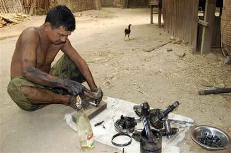 Win Maung attempts to repair the diesel motor for his private generator that supplies electricity to more than 200 homes in the village of Kya-oh in Myanmar April 1, 2012. Despite being located at the historical heart of Myanmar's oil sector, Kya-oh and numerous other poverty-stricken villages near the tourist haven of Bagan do not receive public electricity, but must depend instead on their own limited funds to keep the lights on at night. Picture taken April 1, 2012. To match Insight MYANMAR-ENERGY/ REUTERS/Staff
