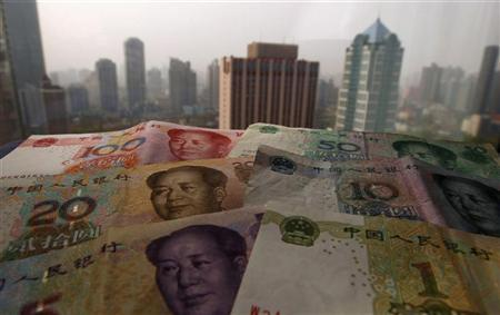 Different values of China's yuan banknotes are placed on a window sill as Shanghai's skyscrapers are seen in the background, in this photo illustration taken in Shanghai April 15, 2012. China's weekend reform of its currency regime nails shut the coffin on the last remains of doubt about whether the world's second biggest economy has successfully steered a course past a hard economic landing. REUTERS/Petar Kujundzic
