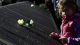 A girl places a rose on a plaque bearing the names of those who died when the Titanic sank, at the unveiling of the Titanic Memorial Garden in Belfast's City Hall April 15, 2012. REUTERS/Cathal McNaughton