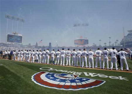 The Los Angeles Dodgers line up during the pre-game ceremonies before their MLB national league baseball game home opener against the Pittsburgh Pirates in Los Angeles April 10, 2012. REUTERS/Danny Moloshok