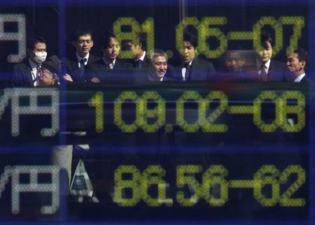 People are reflected on an electronic board displaying exchange rates in a business district in Tokyo February 27, 2012. REUTERS/Toru Hanai