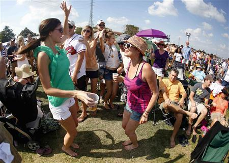Angele Henning (L) dances with Julie Lacoste while enjoying musician Kirmet Ruffins's performance during the 29th annual French Quarter Festival in New Orleans, Louisiana April 14, 2012. REUTERS/Sean Gardner
