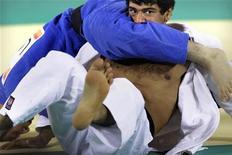 """Мухмадмурод Абдурахомов из Таджикистана (в белом) борется со спортсменом из Узбекистана Рамзиддином Саидовым на соревнованиях по дзюдо в рамках 16-х Азиатских игр в Гуанчжоу 13 ноября 2010. Узбекистан возобновил поставки газа в соседний Таджикистан после полумесячной паузы, которую Душанбе назвал """"политическим давлением"""" и """"блокадой"""", а аналитики сочли демонстрацией силы Ташкента, готовящегося к торгу с Западом о путях вывода войск из Афганистана. REUTERS/Jason Lee"""