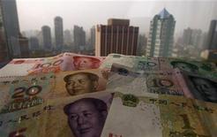 Банкноты китайского юаня на фоне небоскребов в Шанхае, 15 апреля 2012 г. Реформа валютного режима Китая, проведенная на выходных, уничтожила последние сомнения в том, что вторая по величине экономика мира успешно держит курс мимо жесткой посадки. REUTERS/Petar Kujundzic