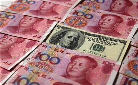 A U.S. $100 banknote is placed next to 100 yuan banknotes in this picture illustration taken in Beijing in this October 16, 2010 file photo. REUTERS/Petar Kujundzic/Files