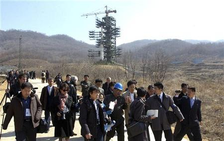 Journalists leave the Unha-3 (Milky Way 3) rocket as it sits on a launch pad during a guided media tour by North Korean authorities at the West Sea Satellite Launch Site in Cholsan, northwest of Pyongyang April 8, 2012 and released by the North's official KCNA news agency in Pyongyang April 9, 2012. REUTERS/KCNA