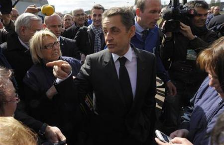 France's President and UMP party candidate for his re-election, Nicolas Sarkozy (C), arrives at the Poitou foundry in Ingrandes, near Poitiers, April 16, 2012. REUTERS/Philippe Wojazer