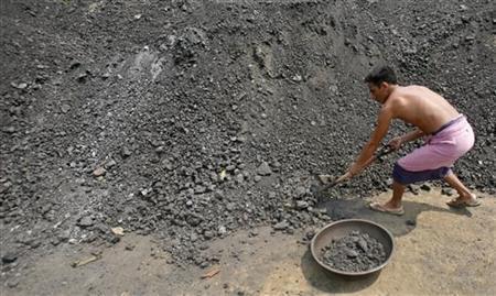 A worker shovels coal at a wholesale coal shop on the outskirts of Agartala, Tripura April 3, 2012. REUTERS/Jayanta Dey