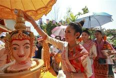 "Nang Sangkhan, or Miss Lao New Year, pours water mixed with frangipanis and perfume over the head of a statue as she takes part in ""Pi Mai Lao,"" or Lao New Year celebrations in Vientiane April 13, 2012. REUTERS/Stringer"
