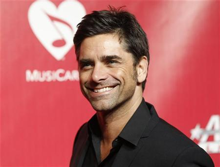 Actor and musician John Stamos poses at the 2012 MusiCares Person of the Year tribute honoring Paul McCartney in Los Angeles February 10, 2012. REUTERS/Danny Moloshok