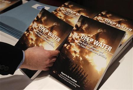 A journalist reaches for a copy of the report by the National Commission on the BP Deepwater Horizon Oil Spill and Offshore Drilling in Washington January 11, 2011. REUTERS/Kevin Lamarque