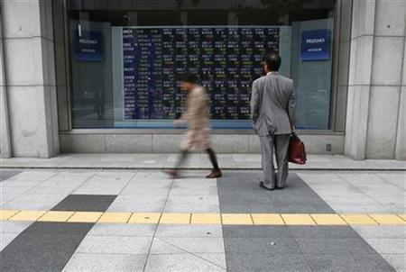 A man looks at a stock quotation board outside a brokerage in Tokyo September 26, 2011. REUTERS/Toru Hanai/Files