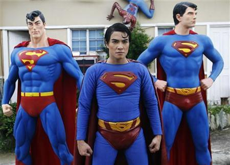 A man poses with his life-sized Superman statues outside his house in Calamba Laguna, south of Manila October 12, 2011. REUTERS/Cheryl Ravelo/Files