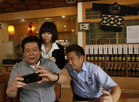 Aida Masayuki (R) and compatriot Tomio Oka review a photo of them taken by a Chinese waitress during lunch at a Japanese restaurant in the township of Zhangan near Dongguan in the southern Guangdong province March 21, 2012. REUTERS/Bobby Yip