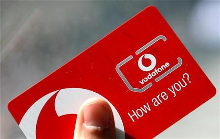 A woman holds a new Vodafone sim card in central London May 30, 2006. REUTERS/Alessia Pierdomenico/Files