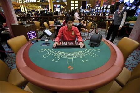 A croupier at a Three-Pictures card table waits for patrons at the newly opened Ladies Club section of Resorts World Casino in Singapore July 15, 2010. REUTERS/Tim Chong