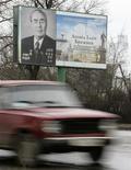 """Автомобиль Lada проезжает мимо портрета Брежнева в Днепродзержинске 26 января 2007 года. Российский автогигант Автоваз во вторник снял с конвейера своего завода Ижавто последнюю массовую """"классическую"""" модель Lada 2107, разработанную советскими инженерами больше 30 лет назад. REUTERS/Gleb Garanich"""