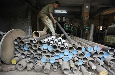 A worker checks an iron pipe that will be used to make spare parts for a drilling machine inside a factory in Kolkata March 12, 2012. REUTERS/Rupak De Chowdhuri/Files