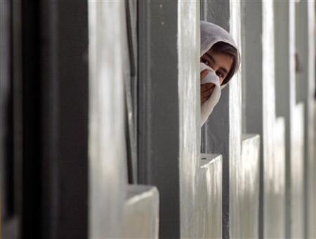 A young Pashtun girl looks out from the window of a classroom during recess at a government funded coeducational school in the southern Afghan city of Kandahar September 20, 2005. REUTERS/Adrees Latif/Files