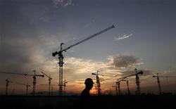 A worker walks past a residential construction site as the sun sets behind construction cranes on the outskirts of Beijing August 18, 2011. REUTERS/Soo Hoo Zheyang
