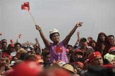 Supporters of Myanmar's pro-democracy of Aung San Suu Kyi wave their hands and National League for Democracy party flags at a ceremony to mark Myanmar's New Year Day in her constituency of Kawhmu township April 17, 2012. REUTERS/Soe Zeya Tun