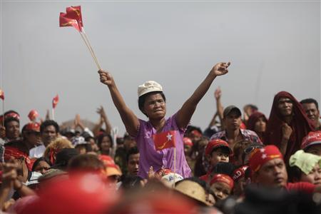 Supporters of Myanmar's pro-democracy of Aung San Suu Kyi wave their hands and National League for Democracy party flags at a ceremony to mark Myanmar's New Year Day in her constituency of Kawhmu township April 17, 2012. REUTERS-Soe Zeya Tun