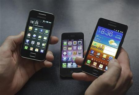 A man holds a Samsung S II (R) and Samsung Ace (L) smartphones next to an Apple iPhone 4 in Houten in this photo illustration August 24, 2011. REUTERS/Michael Kooren/Files