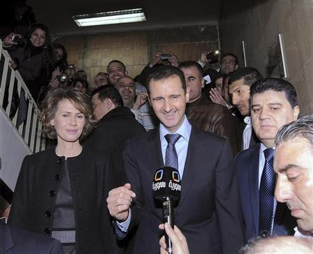 Syria's President Bashar al-Assad and his wife Asma speak to the media after voting at a referendum on a new constitution at a polling station at a Syrian TV station building in Damascus February 26, 2012, in this handout photograph released by Syria's national news agency SANA. REUTERS/SANA